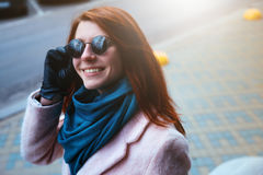 Red haired beautiful girl is walking by the street in a pink coat and blue scarf, with sunglasses. Stock Photos