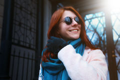 Red haired beautiful girl is walking by the street in a pink coat and blue scarf, with sunglasses. Royalty Free Stock Photography
