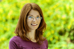 Red-haired beautiful young woman. Portrait of red-haired smiling beautiful young woman with glasses, against green of summer park Royalty Free Stock Image