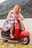 Red-haired beauty with overweight on a red scooter Royalty Free Stock Image