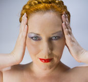 The red-haired blue-eyed woman. Portrait of a red-haired blue-eyed woman keeps hands to temples Royalty Free Stock Images