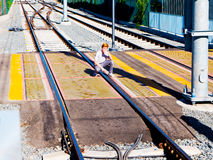 Red Haired Boy Crouched Over Light Rail Crosswalk Next To Metro Light Rail Platform. Red haired boy crouching over light rail Stock Photos