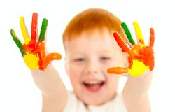 Red-haired boy with focused painted hands Stock Images
