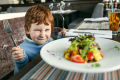 Red haired boy with forks eating salad Royalty Free Stock Photos