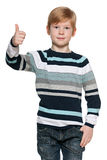 Red-haired boy holds his thumb up Stock Images