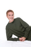 Red haired boy leaning on his side. Attractive teenage boy with red hair, freckles, and sideburns Stock Photos