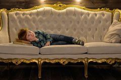 Red-haired boy is lying on the couch.  Royalty Free Stock Photos