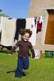 Red haired boy running in garden Stock Photo