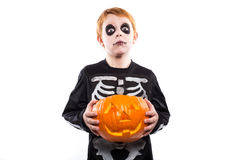 Red haired boy in skeleton costume holding a pumpkin. Halloween Royalty Free Stock Image
