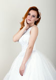 Red-haired bride in a wedding dress, bright unusual appearance. Beautiful hairstyle and professional make-up Stock Photos