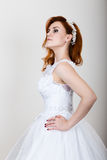 Red-haired bride in a wedding dress, bright unusual appearance. Beautiful hairstyle and professional make-up Stock Photo