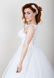 Red-haired bride in a wedding dress, bright unusual appearance. Beautiful hairstyle and professional make-up Stock Photography