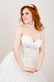 Red-haired bride in a wedding dress, bright unusual appearance. Beautiful wedding hairstyle and bright make-up Royalty Free Stock Images