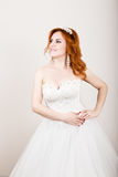 Red-haired bride in a wedding dress, bright unusual appearance. Beautiful wedding hairstyle and bright make-up Stock Photo