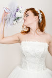 Red-haired bride in a wedding dress holding wedding bouquet, bright unusual appearance. Beautiful wedding hairstyle and Royalty Free Stock Photos