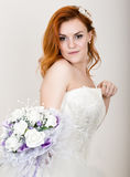 Red-haired bride in a wedding dress holding wedding bouquet, bright unusual appearance. Beautiful wedding hairstyle and Stock Photography