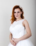 Red-haired bride in a wedding dress holding wedding bouquet, bright unusual appearance. Beautiful wedding hairstyle and Stock Images