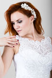 Red-haired bride in a wedding dress holding wedding bouquet, bright unusual appearance. Beautiful wedding hairstyle and Royalty Free Stock Photo