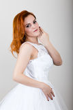 Red-haired bride in a wedding dress holding wedding bouquet, bright unusual appearance. Beautiful wedding hairstyle and Stock Photos
