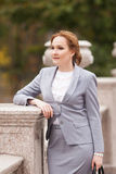 Red haired business women in grey suit. Red haired business woman in grey suit on smooth background Stock Images