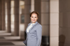 Red haired business women in grey suit. Red haired business woman in grey suit on the wind on smooth background Royalty Free Stock Image