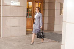 Red haired business women walking. Red haired business woman walking on smooth background Stock Photos