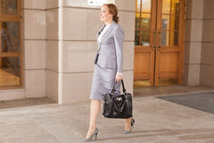 Red haired business women walking. Red haired business woman walking on smooth background Royalty Free Stock Image