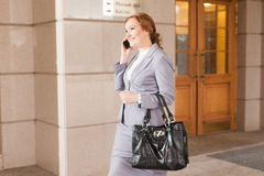 Red haired business women walking. Red haired business woman walking and talking by phone on smooth background Royalty Free Stock Photo