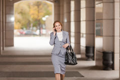 Red haired business women walking. Red haired business woman walking and talking by phone on smooth background Stock Photo