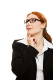 Red-haired businesswoman with glasses dreams. Royalty Free Stock Photography
