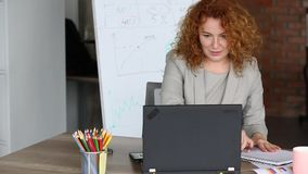 Red haired businesswoman in a hurry at working place. stock video