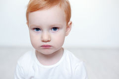 Red-haired child with big blue eyes. Against a white wall with copyspace Royalty Free Stock Photo