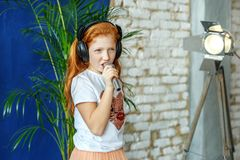 A red-haired child sings a song in a microphone. The concept is. Childhood, lifestyle, music, singing, listening, hobbies Royalty Free Stock Images