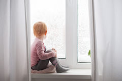 The red-haired child is sitting on window Royalty Free Stock Image