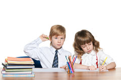 Red-haired children are writing at the desk Royalty Free Stock Image