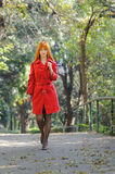Red haired coated young girl walking on the leaf road Royalty Free Stock Photo