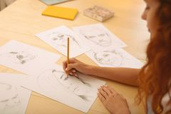 Red-haired creative person drawing caricatures. Drawing caricatures. Red-haired appealing creative person feeling extremely cheerful while drawing caricatures royalty free stock image