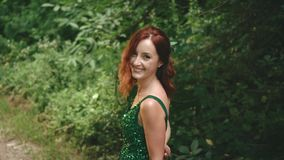 The red-haired, curly girl in the green emerald dress smiles and laughs at the camera. Funny masquerade fashion woman. Positive emotions. background nature stock footage