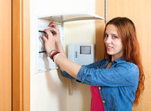 Red-haired cute woman turning off the light-switch at power cont Royalty Free Stock Photos