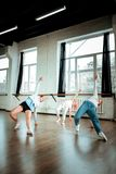 Red-haired dance teacher in blue jeans and her students doing arching. Being flexible. Red-haired dance teacher wearing blue jeans and her students doing arching stock photography