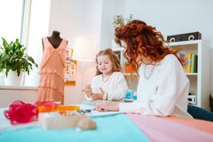 Red-haired designer designing sketches with her lovely girl. Designing sketches. Red-haired designer designing sketches with her lovely girl joining her at work stock images