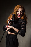 Red-haired diva singing song Stock Photo