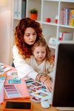 Red-haired fashion designer working on computer sitting with daughter. Sitting with daughter. Red-haired fashion designer working on computer while sitting with royalty free stock image