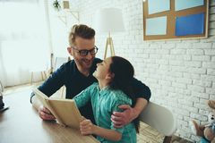 Red haired father reads book with teenage daughter royalty free stock photography