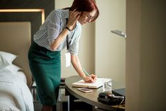 Red-haired female designer noting details of work during phone conversation. Red-haired female designer noting details of work during phone conversation in stock photos