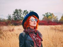 Red-haired female in a park stock photos