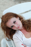 Red haired female relaxing on chaise Royalty Free Stock Photography