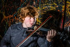 Red-haired freckled boy playing violin with different emotions o royalty free stock photos