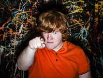 Red-haired freckled boy showing to youwith serious face Royalty Free Stock Photography