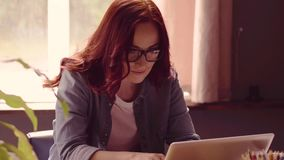 Red haired freelancer woman working on laptop. stock footage